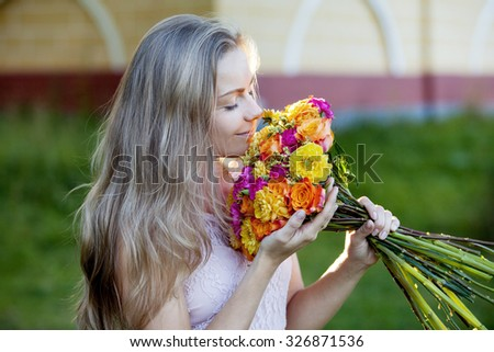 Young beautiful woman with a bright bouquet, girl smelling  flowers - stock photo