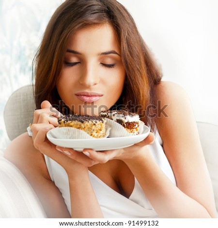 Young beautiful woman with a cake. Closeup portrait. Sitting on sofa at her home - stock photo