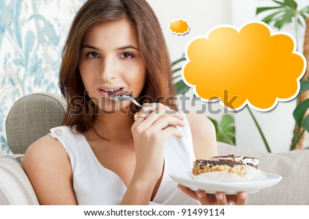 Young beautiful woman with a cake. Closeup portrait. Sitting on sofa at her home. Blank cloud balloon for her thoughts. - stock photo