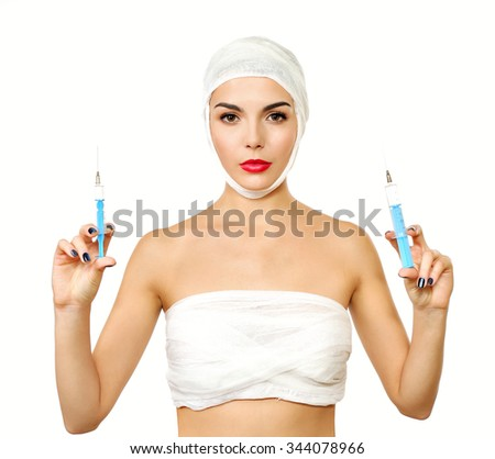 Young beautiful woman with a gauze bandage on her head and chest, holding syringe, isolated on white