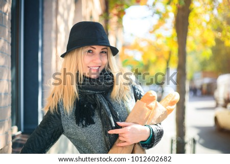 Young beautiful woman with a loaf of bread in her hands in autumn outdoors