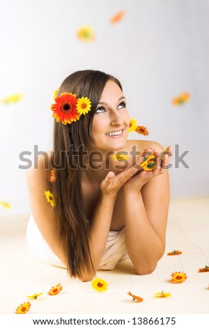 young beautiful woman with a towel and falling flowers