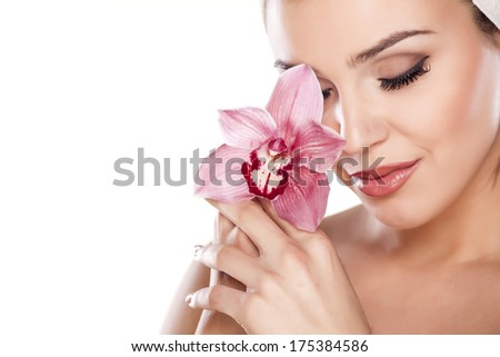 young beautiful woman with a towel on her head posing with orchid