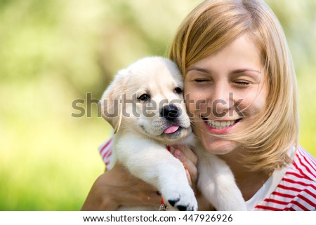young beautiful woman with a white puppy labrador retrievers. dogs and woman. outdoor portrait. Beautiful woman playing with her dog.