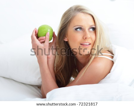 Young beautiful woman with apple in bed in the morning