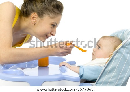 Young, beautiful woman with baby. Baby is sitting on baby's chair. Mother is feeding him. White background, side view - stock photo