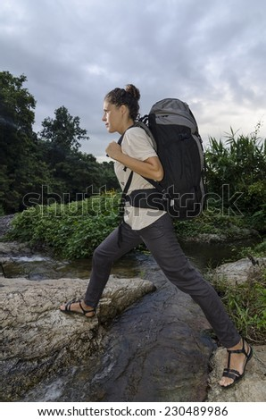 Young beautiful woman with backpack crossing the stream in the forrest