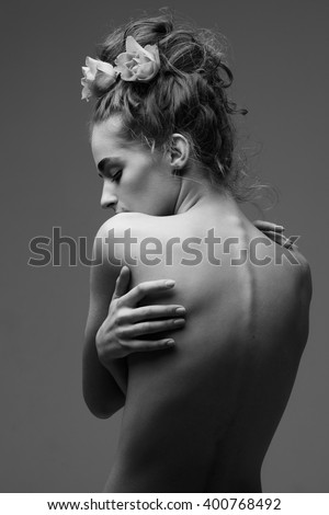 Young beautiful woman with beautiful hairstyle hugging herself