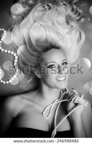 Young beautiful woman with blond curly hair holding pearls in her hand - stock photo