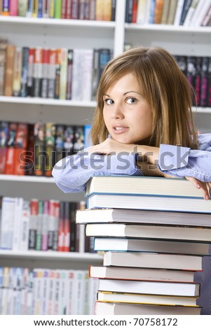 Young beautiful woman with books for reading in the library