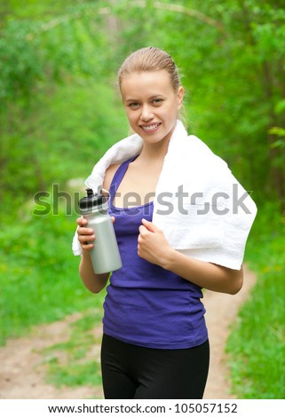 Young beautiful woman with bottle of water after fitness exercise outdoors - stock photo