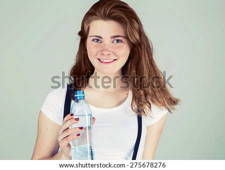 Young beautiful woman with bottle of water studio portrait fresh  - stock photo