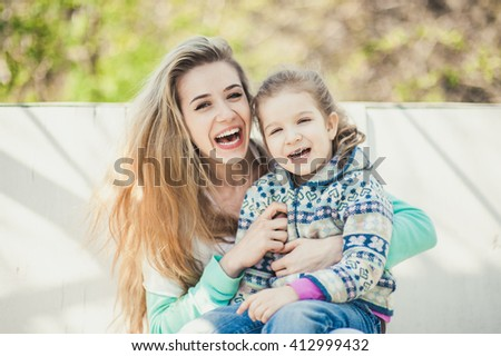 Young beautiful woman with child laugh and smile sitting on the white wood bench  - stock photo