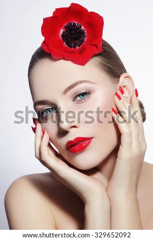 Young beautiful woman with clean make-up, red lips, fancy manicure and red flower in her hair - stock photo