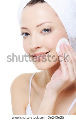 young beautiful woman with cotton swab cleaning her face - stock photo