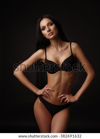 Young beautiful woman with dark straight hair, almond-shaped eyes and tanned skin in the black seamless underwear collection is posing in the studio on the black background
