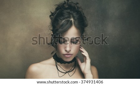 young beautiful woman with dark wavy hair pulled into a bun portrait, studio shot