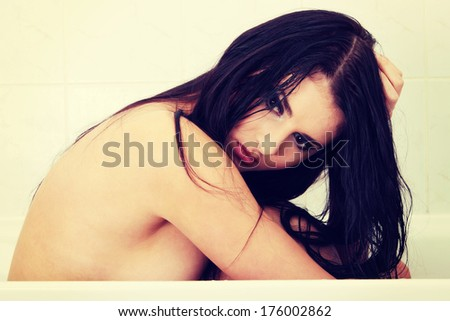 Young beautiful woman with depression sitting nude in bathroom (sexual abuse concept) - stock photo