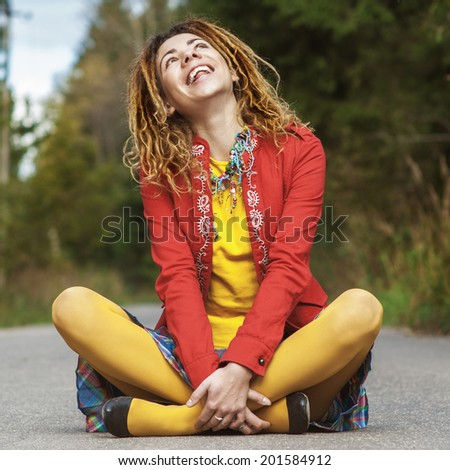 Young beautiful woman with dreadlocks in red clothes sitting on pavement in lotus position and laughs. - stock photo