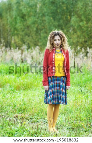 Young beautiful woman with dreadlocks in red clothes standing in park on grass. - stock photo