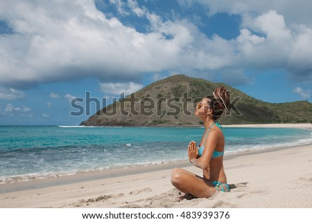 Young beautiful woman with dreadlocks wearing light blue bikini practicing meditation on tropical white sand beach during yoga retreat on island vacation