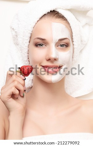 young beautiful woman with facial mask and strawberry, spa treatment
