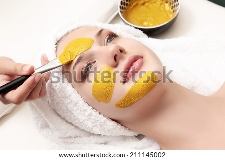 young beautiful woman with facial mask, spa treatment - stock photo