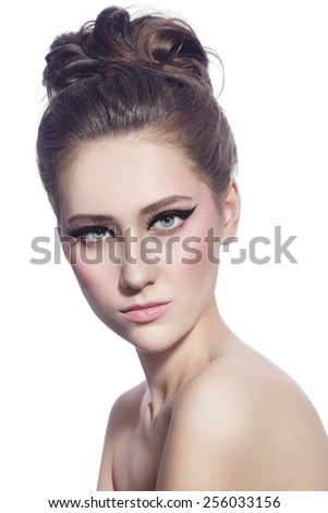 Young beautiful woman with fancy cat eye make-up and stylish hairdo over white background - stock photo