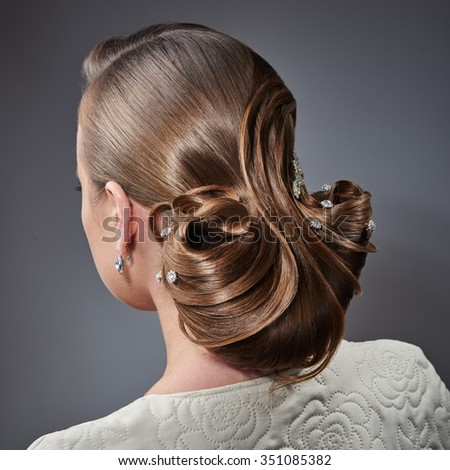 Young beautiful woman with fashion evening hairstyle posing in the studio - stock photo