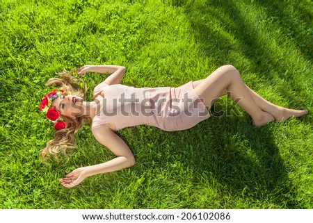 Young beautiful woman with flower wreath lying down on grass - stock photo