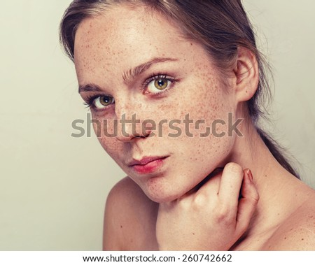 young beautiful woman with freckles portrait studio on light background hipster  - stock photo