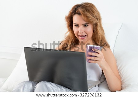 Young beautiful woman with funny face sitting at her bedroom with laptop and cup of tea carried away with something she searches online.