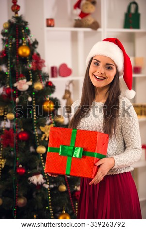 Young beautiful woman with gift celebrating Christmas at home - stock photo