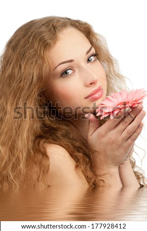 Young beautiful woman with healthy skin and long curly hair holding pink flower in her hands.Beauty treatment concept  - stock photo