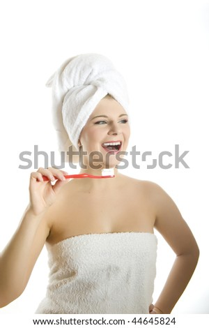 Young beautiful woman with healthy strong teeth and white towel on her head holding tooth brush in bathroom