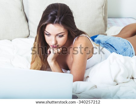 Young beautiful woman with laptop notebook on bed in bedroom home surfing internet