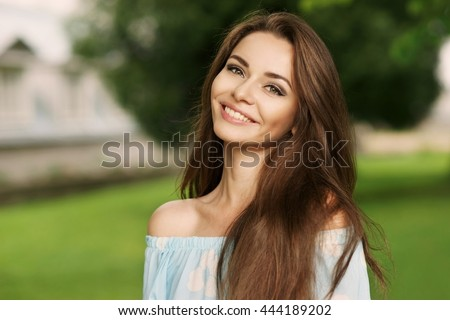 Young beautiful woman with long brunette hair and perfect smile. Happy girl posing in park and looking in camera - stock photo