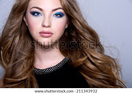 young beautiful woman with long curly hair and blue make up - stock photo