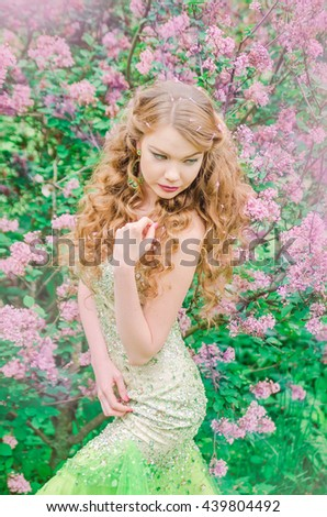 Young beautiful woman with long curvy white hair in a long light green dress is walking in the park among lilac bushes, touching her hair, looking down and dreaming - stock photo