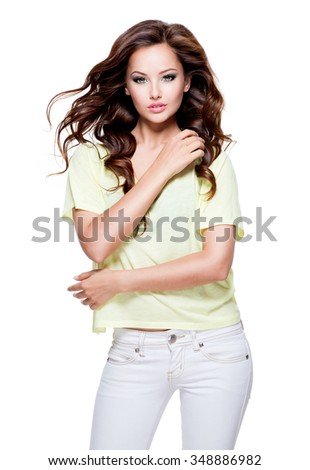 Young beautiful woman with long  hair posing over white background. Full portrait of a pretty fashion model at studio. - stock photo