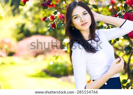 Young beautiful woman with long straight dark hair posing in spring garden - stock photo