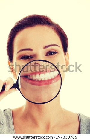Young beautiful woman with magnifying glass - stock photo