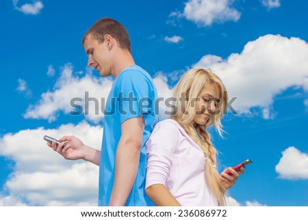 Young beautiful woman with man reading sms on blue summer sky. - stock photo