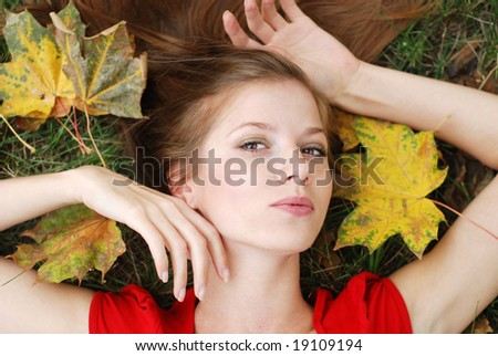 young beautiful woman with maple leaf around her face