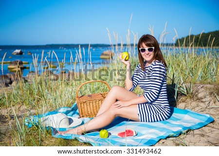 young beautiful woman with picnic basket sitting on the beach