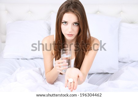 Young beautiful woman with pills on bed close-up - stock photo