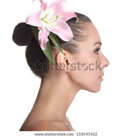 young beautiful woman with pink flower in a profile - stock photo