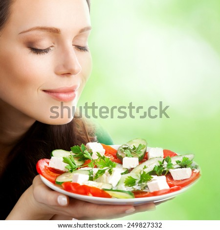 Young beautiful woman with plate of salad, outdoor - stock photo
