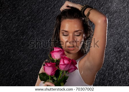 Young beautiful woman with roses stands under rain on a black background. - stock photo