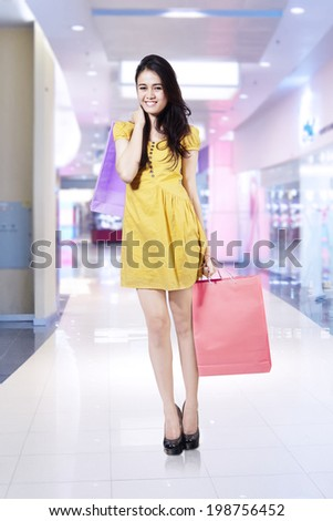 Young beautiful woman with shopping bags in shopping centre